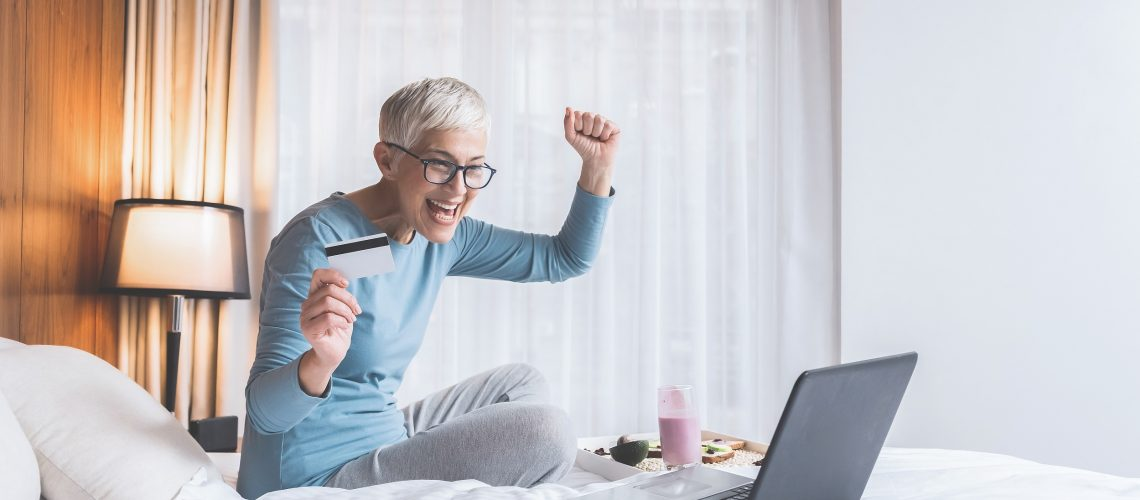 Positive joyful mature woman full of energy and optimism looking at her laptop with credit card in her hand, Online sales and shopping concept